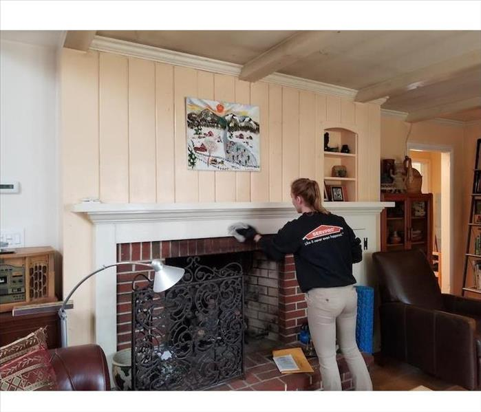 SERVPRO tech cleaning fireplace mantle